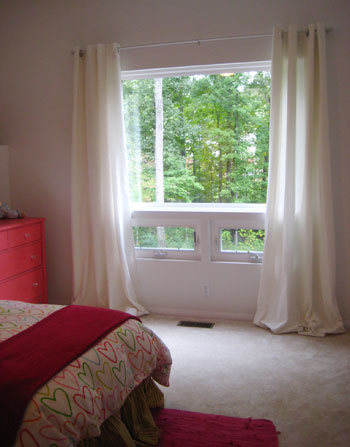 hang curtains wide and high over a window to add polish and style
