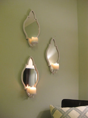 Three Candle Sconces On The Bedroom Wall