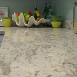 clean kitchen light granite countertop with fruit bowl in background