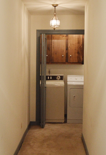Dated laundry room closet at end of a hall with bifold doors, dark cabinets, carpet, and mismatched old washer and dryer