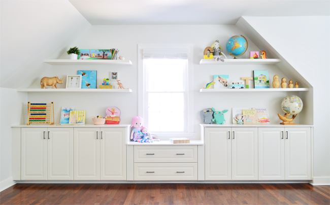 Colorful built-ins filled with toys and games, made from white cabinets and white floating shelves perfect for a kids room, playroom, or bonus room.