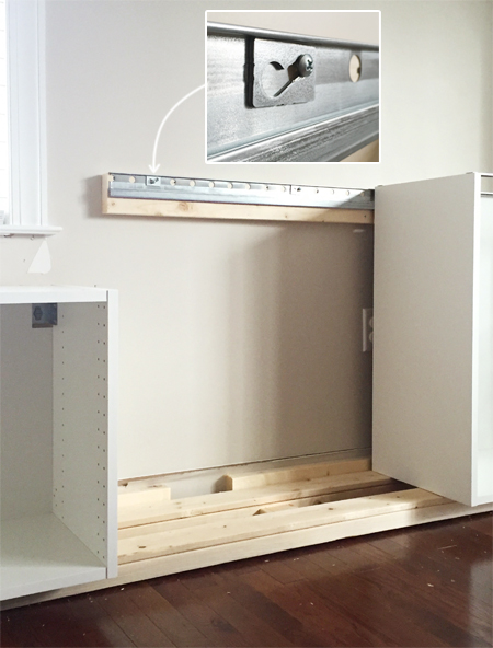detail of how Ikea Sektion cabinets attach to metal wall rail using screw and washer