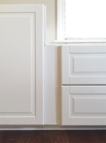 filler piece between two white Ikea Sektion cabinets with Bodbyn doors creating recessed spot between doors and drawers