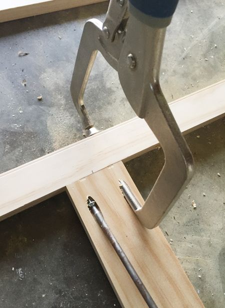 A Kreg jig clamp being used to secure two pieces of wood together at a right angle using a pocket hole screw
