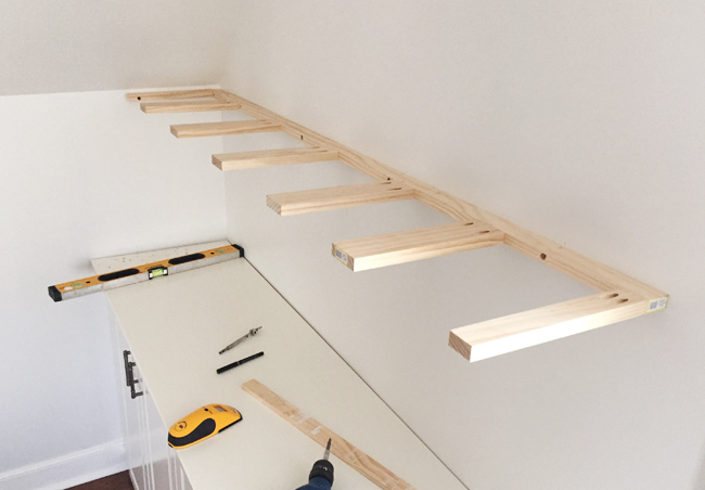 Brace piece of DIY thin wood floating shelves hung on a wall using 1x3 and 1x2 pine boards