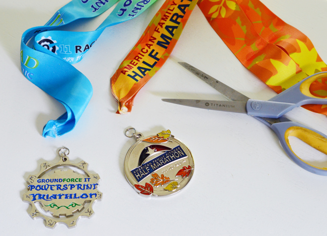 cutting ribbons off of race medals to attach ornament ribbon