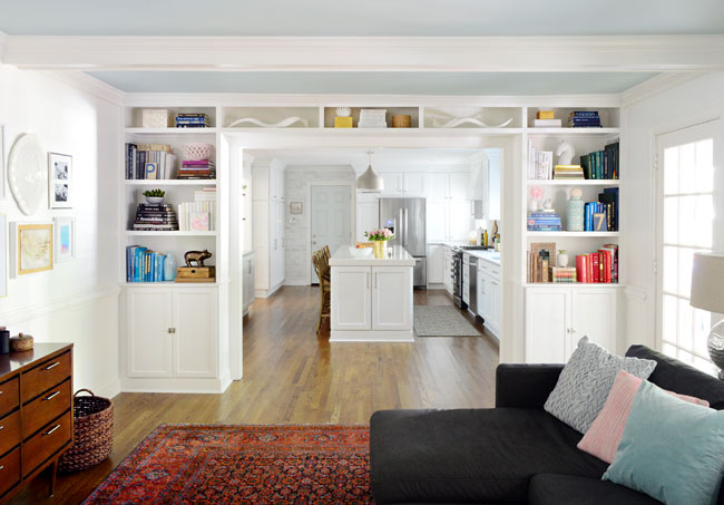 white built-in bookshelves between living room and kitchen