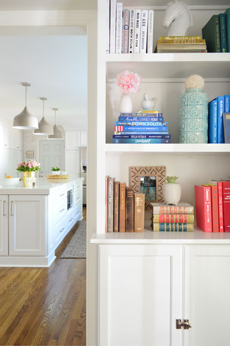 white built-in bookshelves with kitchen in background