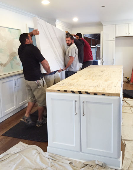 white-kitchen-remodel-carrying-in-double-thick-island