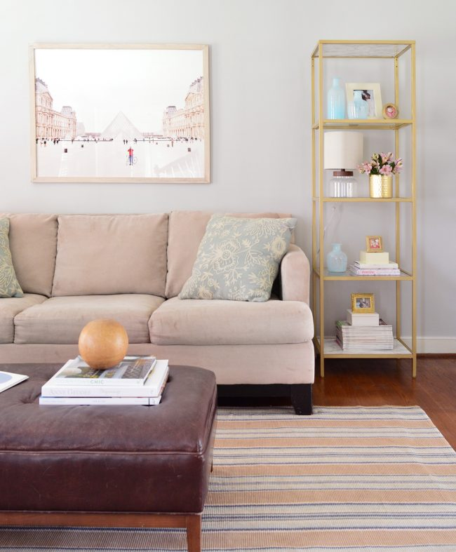 neutral living room with gold shelves and large art