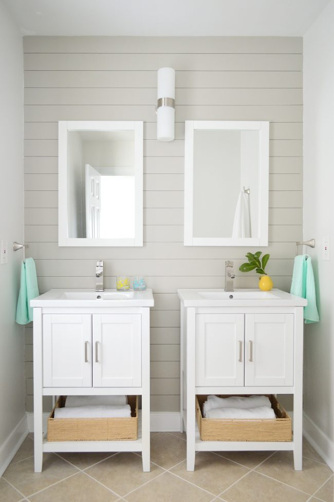 pair of vanities in bathroom staged to sell with gray shiplap wall