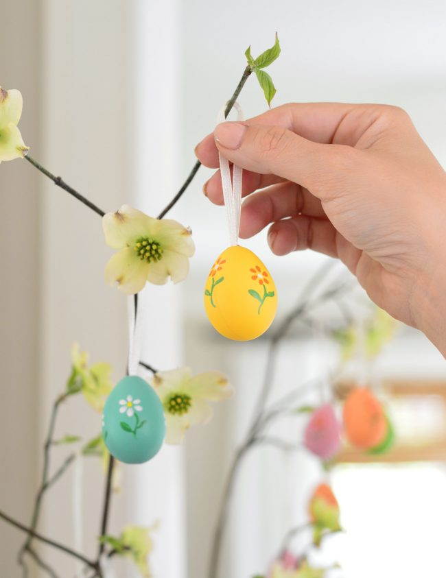 placing decorative painted egg on Easter Tree