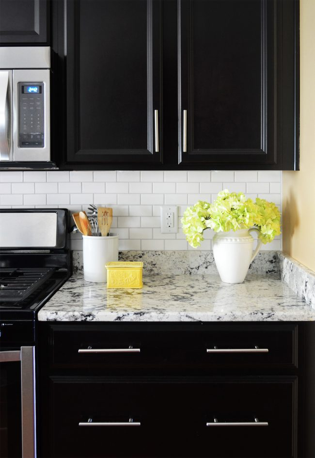 white subway tile backsplash with black cabinets