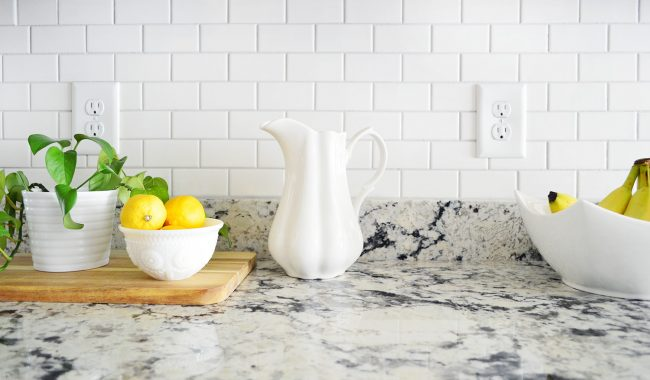 white subway tile kitchen backsplash detail with lemons and pitcher