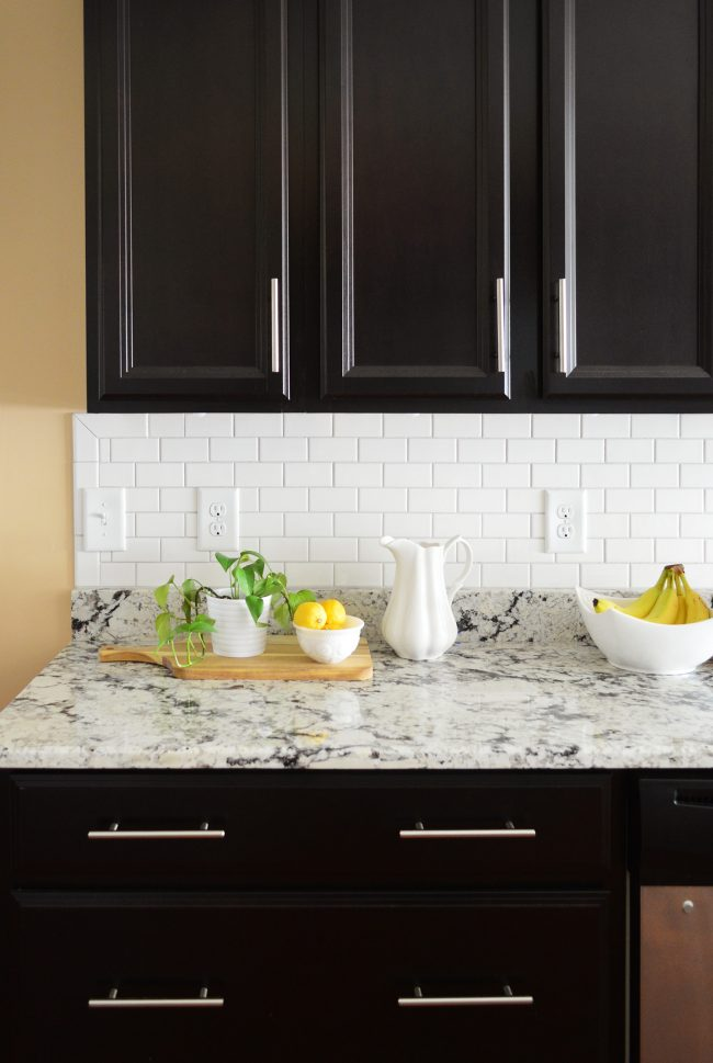 White Subway Tile Sheet Backsplash With Black Cabinetry