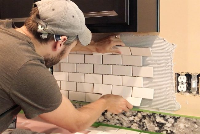 John placing white subway tile sheet onto mastic to set backsplash