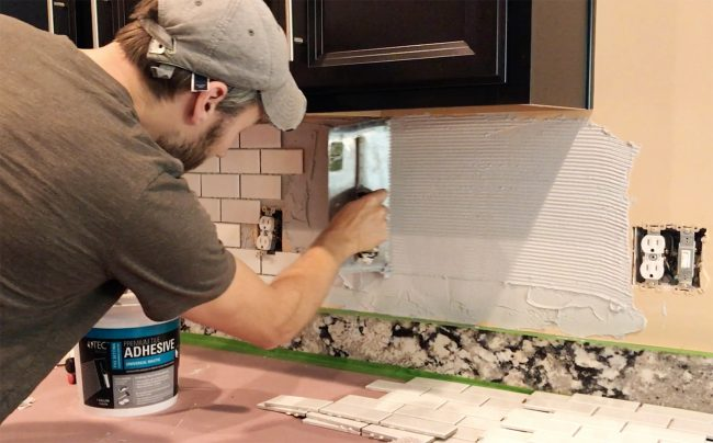 John scraping mastic with v-notch trowel on backsplash wall