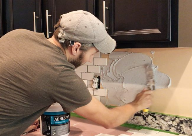 John spreading mastic adhesive on backsplash wall in kitchen