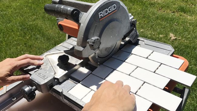 Ridgid wet saw cutting a sheet of small white subway tiles