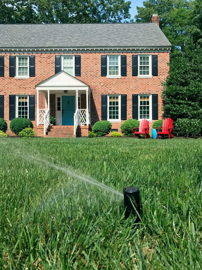 irrigation system sprinkler head spraying lawn close-up
