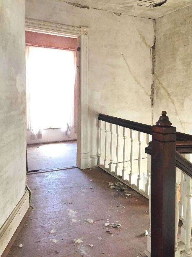 beach house before upstairs landing crumbling drywall painted floor
