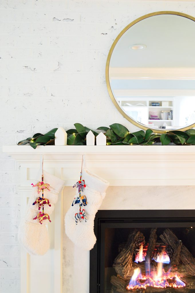 Detail of white traditional fireplace surround with stockings and garland