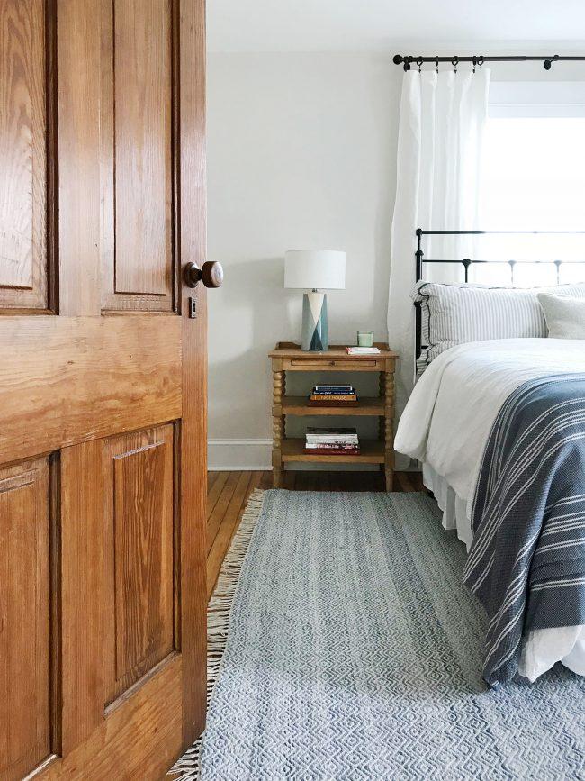 bed in front of window with original pine door