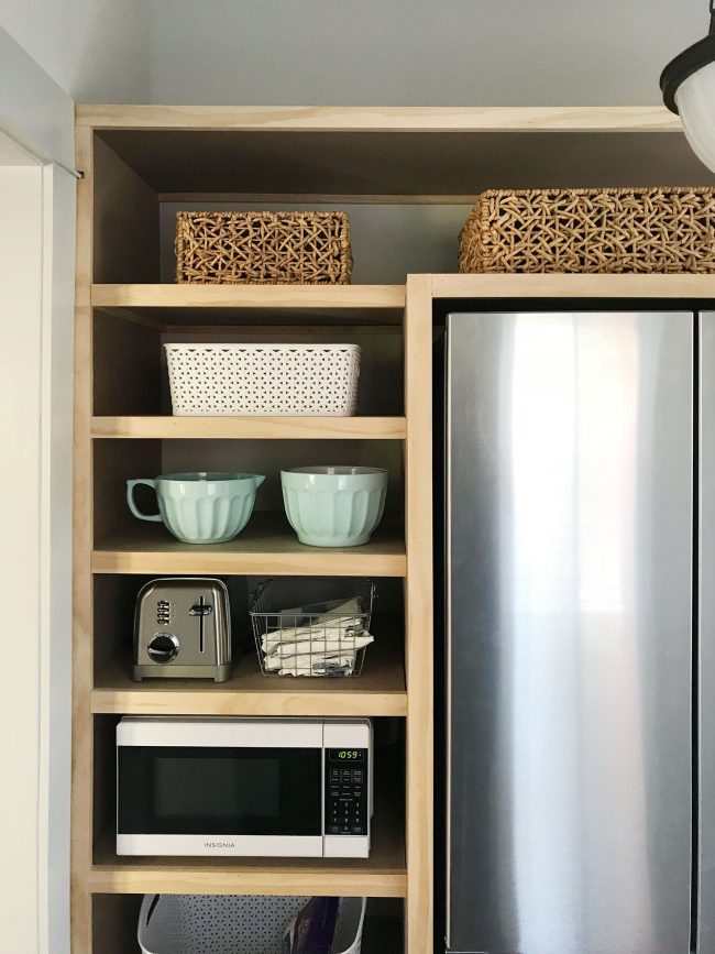 unpainted pantry shelves with baskets and accessories added