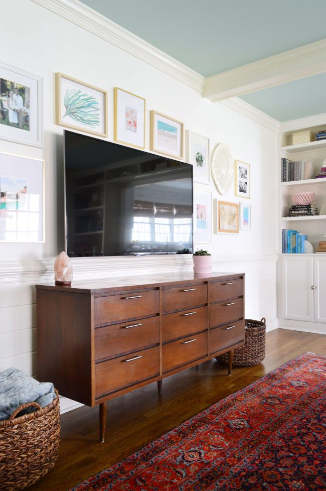 Television Mounted To The Wall With A Picture Frame Gallery Surrounding It