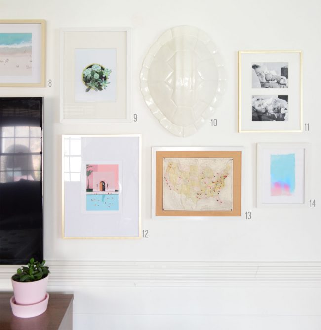 grid of white and gold frames on white gallery wall