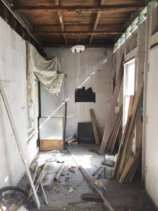 before photo of laundry room with rotting walls and ceilings