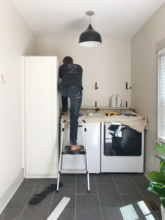 john leaning over top loading washer to screw in shelf brackets