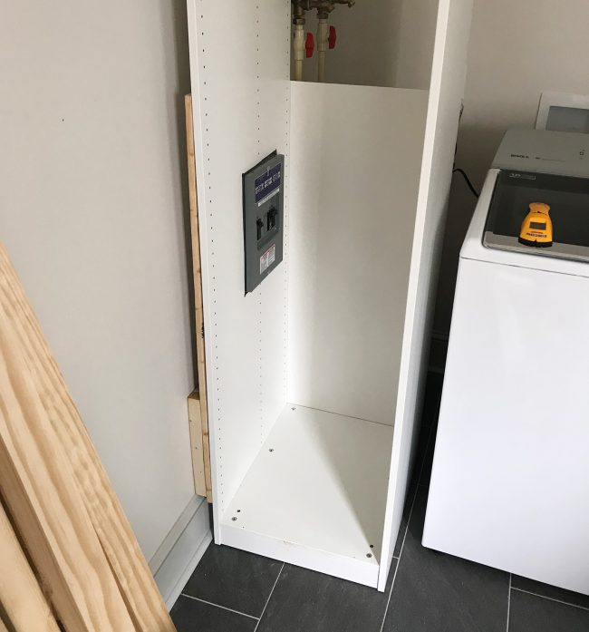 ikea pax wardrobe pressed against wall with cutouts for breaker box
