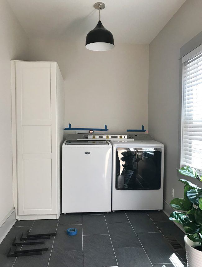 ikea pax wardrobe placed next to top loading washer and dryer in laundry room