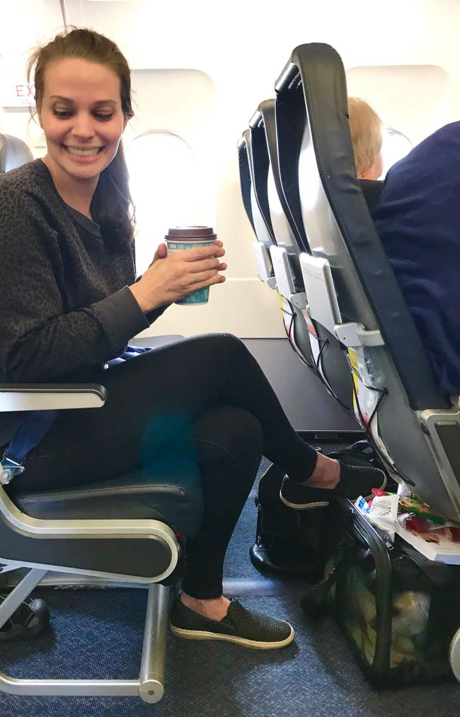 Sherry sitting on plane with dog carrier under seat in front of her