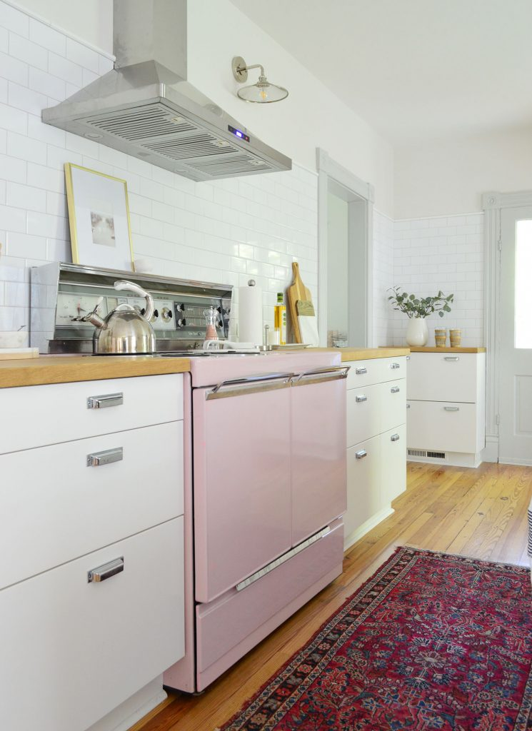 beach house kitchen with pink stove and white subway backsplash
