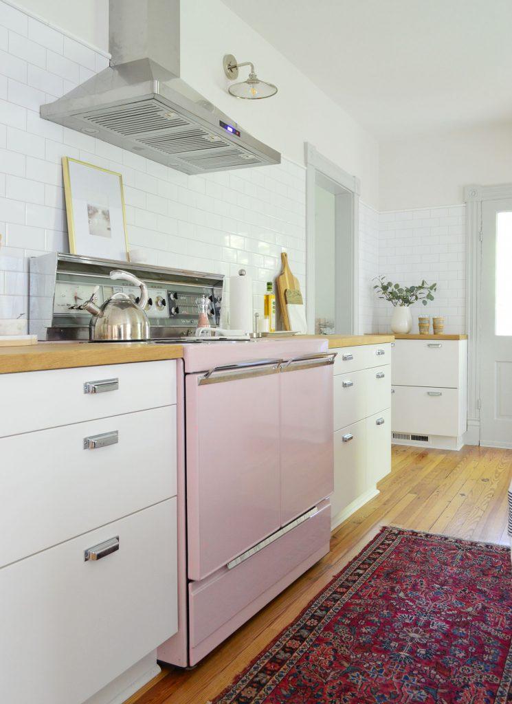 beach house kitchen with pink stove and white subway backsplash