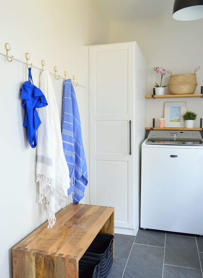 mudroom laundry room with long white coat hook rail