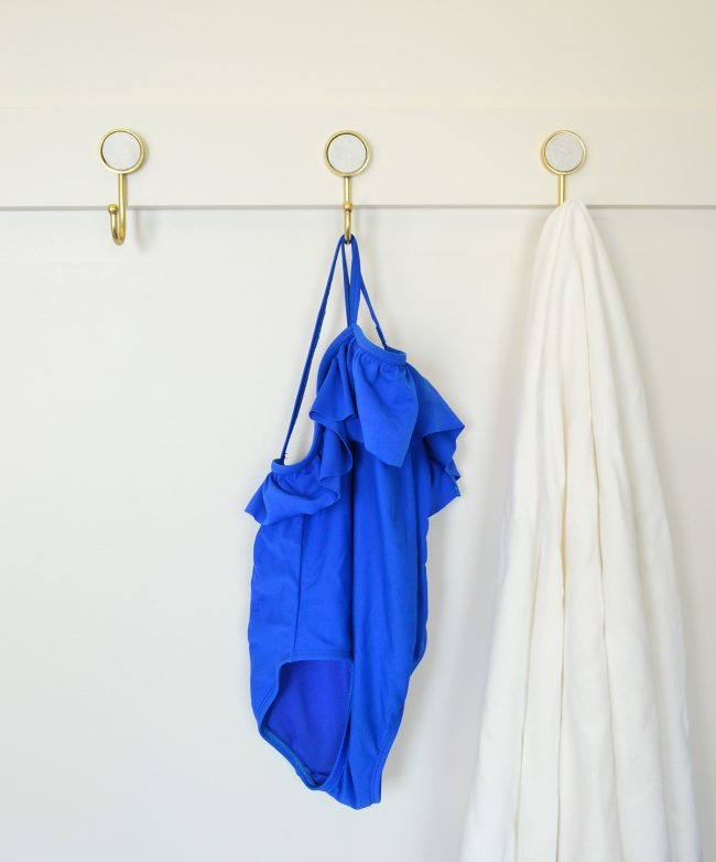 three gold hooks on diy rail with towel and bathing suit