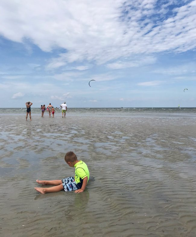 child sitting in shallow and with kiteboarders at cape charles beach