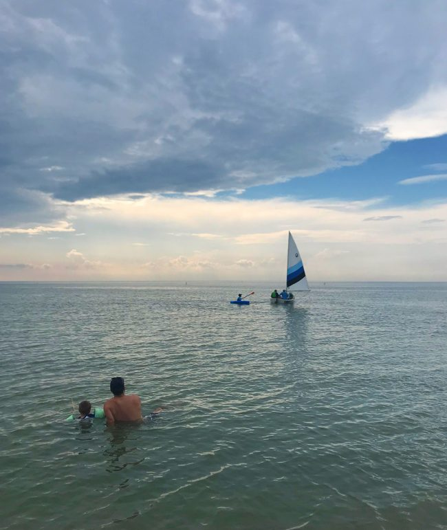 people sitting in water watching sailboat on cape charles beach