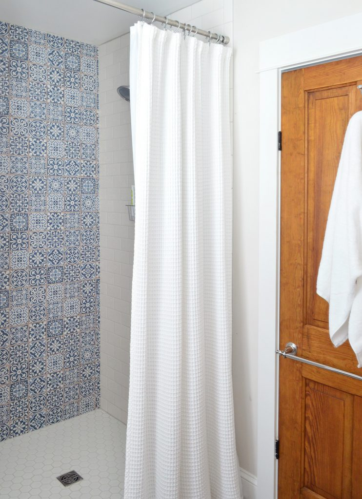 Blue Accent Tile In Shower Of Hall Bathroom With Wood Door