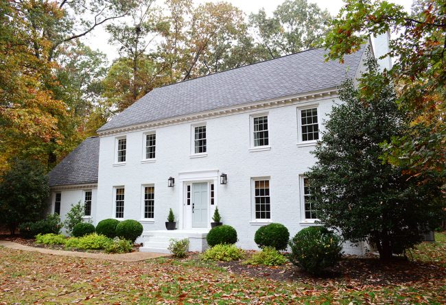 after photo of brick house painted moderne white in fall foliage