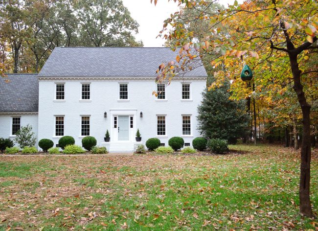 white painted brick house with fall leave and tranquility blue door