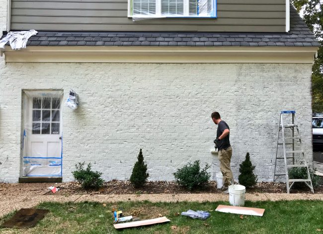 painter rolling a second coat of white paint on a brick house