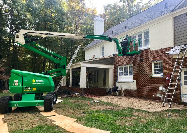 large crane lift used to paint the back of a brick house white