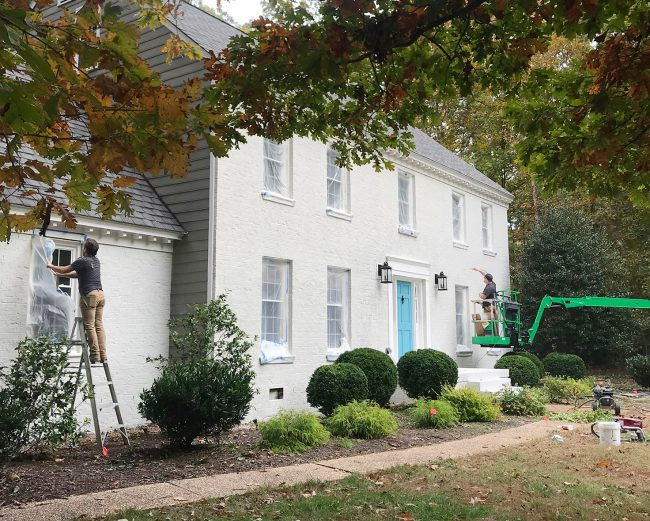 painters applying second coat of romabio biodomus paint to brick house