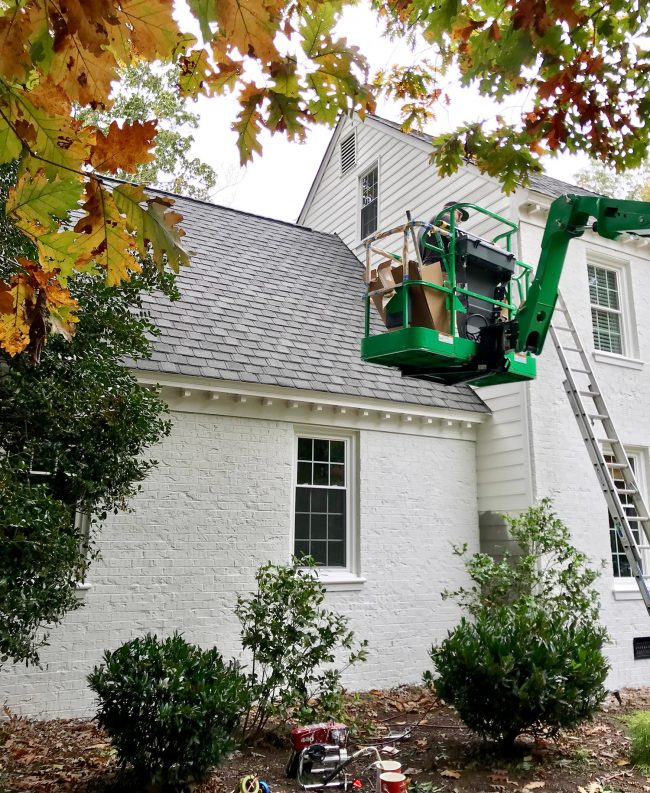 painter in crane painting siding of a brick house white