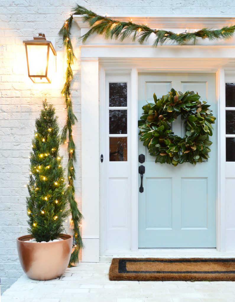 Close Up Of Front Porch With Painted Blue Door Decorated For Christmas