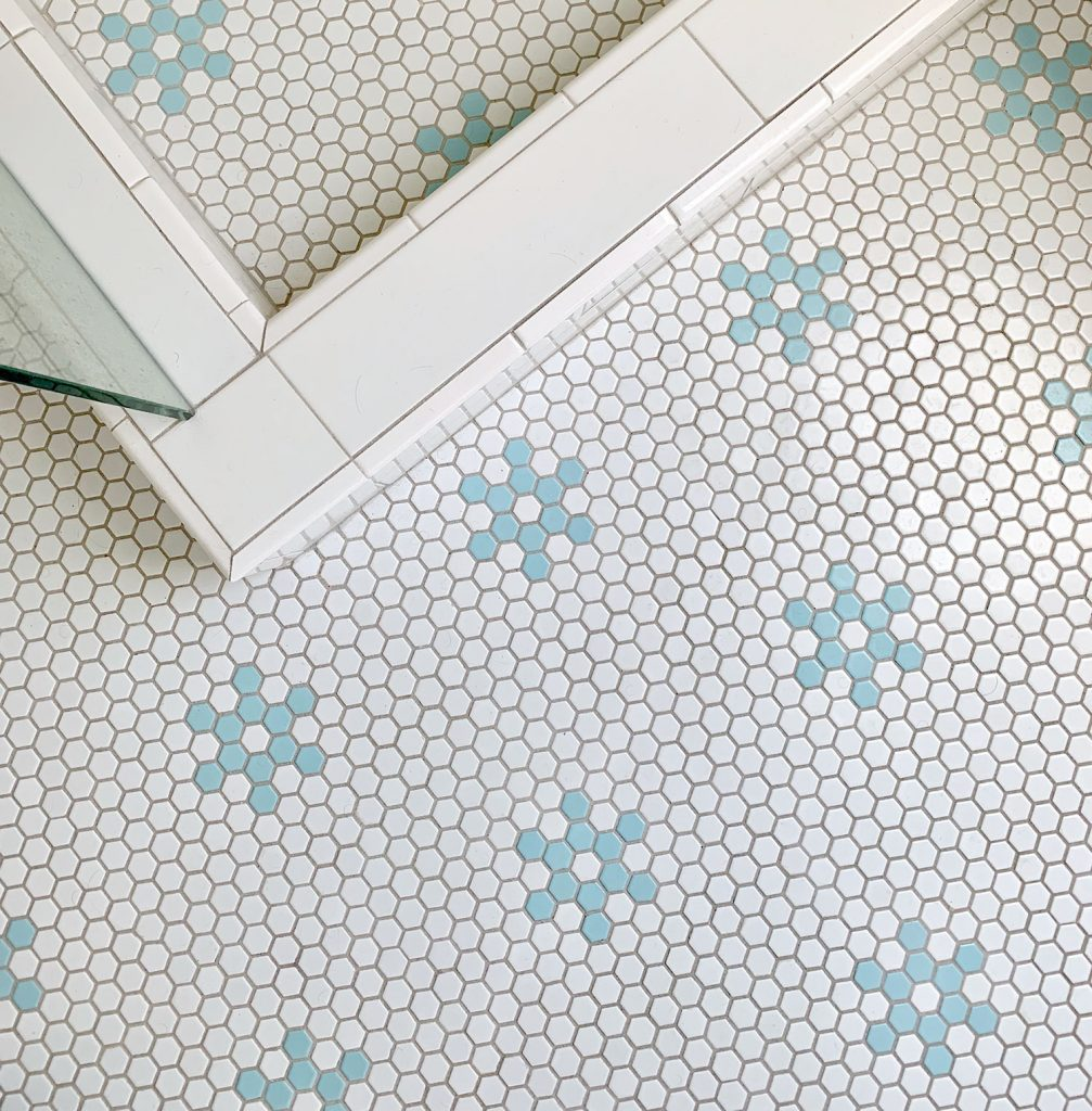 Hex tile bathroom floor with aqua blue flower shapes